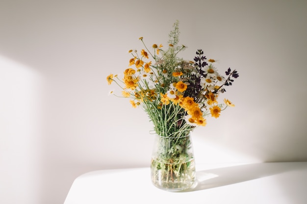 Colorful midsummer bunch of wildflowers in a vase on the table
