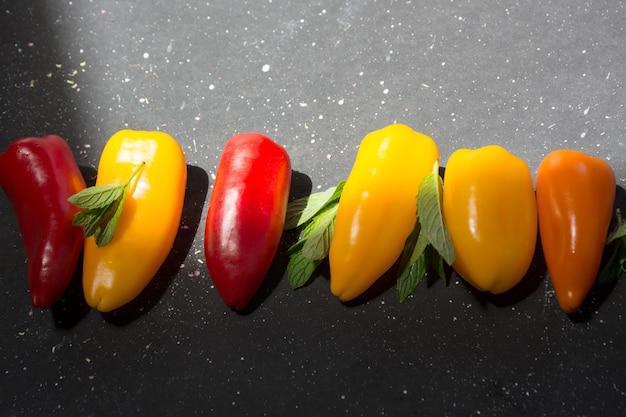 Красочные мини-перцы и листья мяты на черном солнечном фоне. выше вид желтого, красного и оранжевого перца.