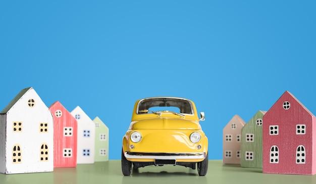 파란색 배경에 다채로운 미니어처 주택과 미니어처 장난감 노란색 복고풍 자동차. 도시의 도시 배경 배너입니다. 복사 공간