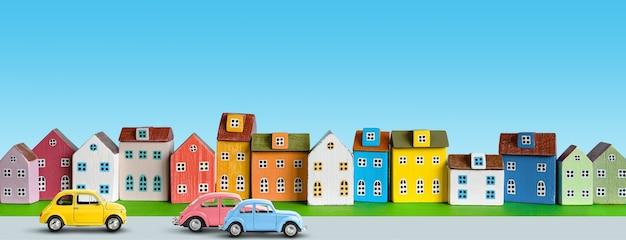 파란색 배경에 줄지어 배열된 다채로운 미니어처 주택. 도시의 도시 배경 배너입니다. 복사 공간
