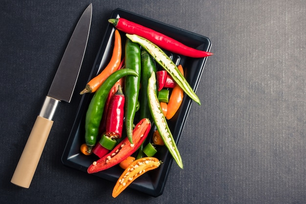 Colorful mix of chili pappers with knife on  black background. free space for text