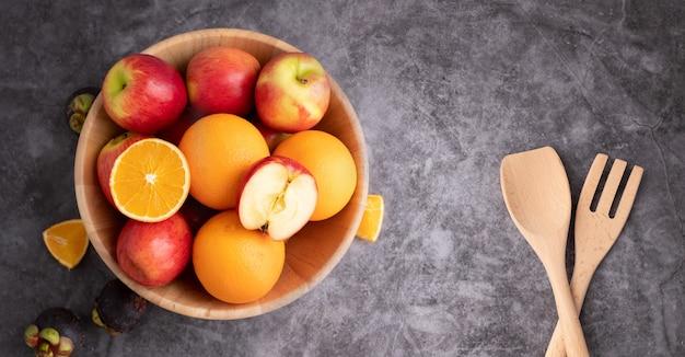 Красочные фрукты микс на деревянной тарелке.