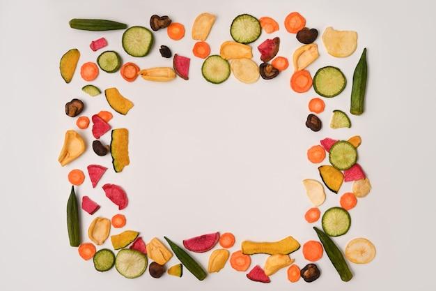 白い背景にオクラ、ニンジン、カボチャ、ビートルート、椎茸とカラフルなミックス野菜チップス。