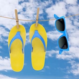 青い空の背景の背景に物干しにぶら下がっている青いサングラスとカラフルなモダンなビーチサンダル。 3dレンダリング