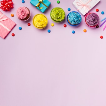 Colorful muffins and gems with wrapped gift boxes on pink backdrop