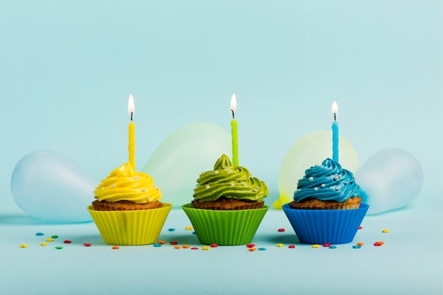 Colorful muffins with candles; sprinkles and balloons on blue backdrop