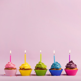 Colorful muffins with lighted candles in a row with sprinkles on pink backdrop