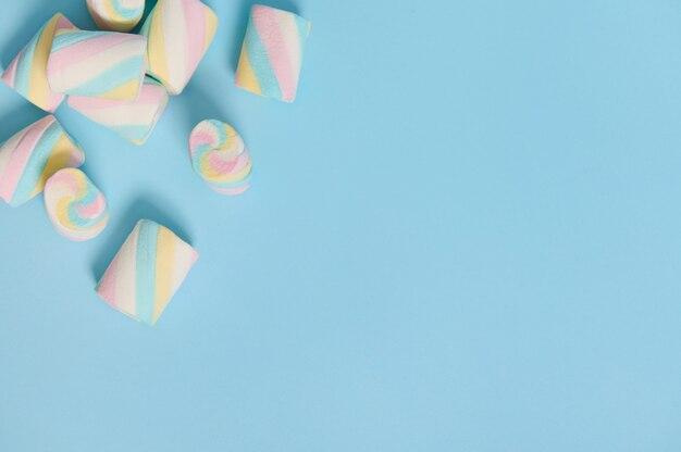 広告用のコピースペースと青いパステルカラーの背景の隅にあるカラフルなマルチカラーの甘いマシュマロ。フラットレイミニマルな構成