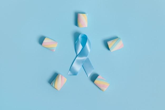 コピースペースのあるパステルカラーの背景に青いアウェアネスリボンが入った五芒星の形に配置されたカラフルなマルチカラーの甘いマシュマロ。 11月14日世界糖尿病デーのコンセプト