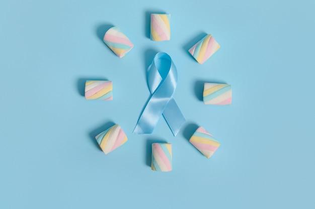 カラフルなマルチカラーの甘い甘いマシュマロが円形に配置され、パステルカラーの背景に青いアウェアネスリボンがあり、広告用のコピースペースがあります。 11月14日の世界糖尿病デーのコンセプト