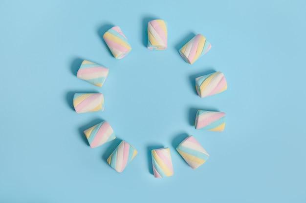 青いパステルカラーの背景に円の形で配置されたカラフルなマルチカラーの甘い甘いマシュマロと広告用のコピースペース。食品の背景。ミニマルなスタイル