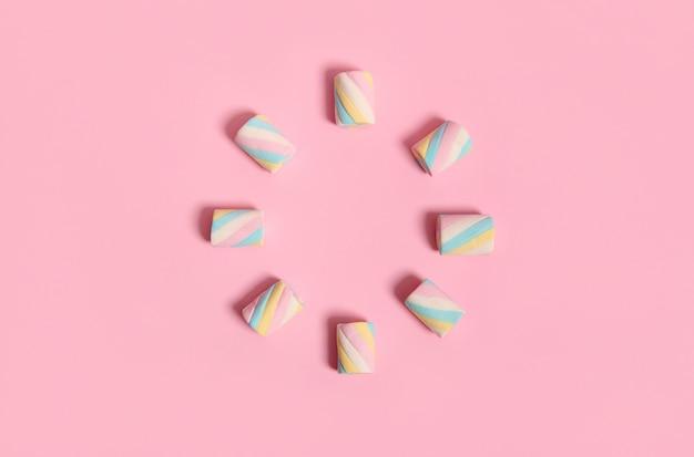 ピンクのパステルカラーの背景に円の形で配置されたカラフルなマルチカラーの甘い甘いマシュマロ。広告用のコピースペースと食品の背景。ミニマルなスタイル、デザイン