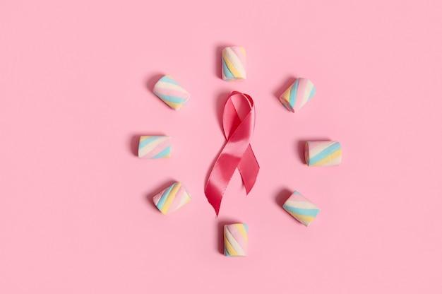 カラフルなマルチカラーの甘い甘いマシュマロが円の形に配置され、パステルカラーの背景にピンクのアウェアネスリボンがあり、広告用のコピースペースがあります。乳がん啓発デーのコンセプト