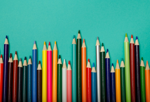 Colorful multicolor pencils arranged in a wave over blue background