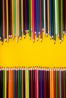 Colorful multicolor pencils on yellow background. top view, copy space