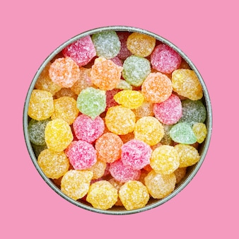Colorful multicolored sucking sweets montpensier lollipops in a round tin box isolated on pink