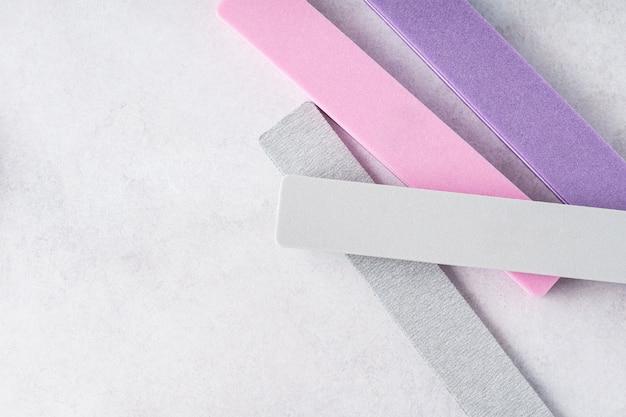 Красочные пилочки для ногтей на сером фоне. инструменты для маникюра и педикюра.