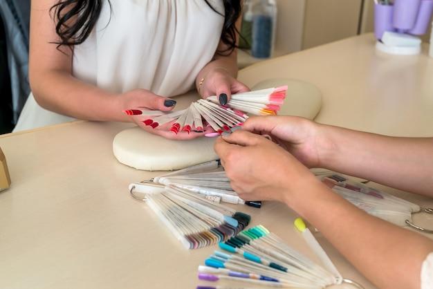 Красочная палитра ногтей в женских руках крупным планом