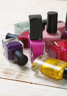 Colorful nail polish bottles on light wooden board