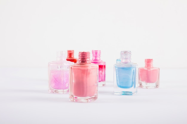Colorful nail polish bottles on white surface
