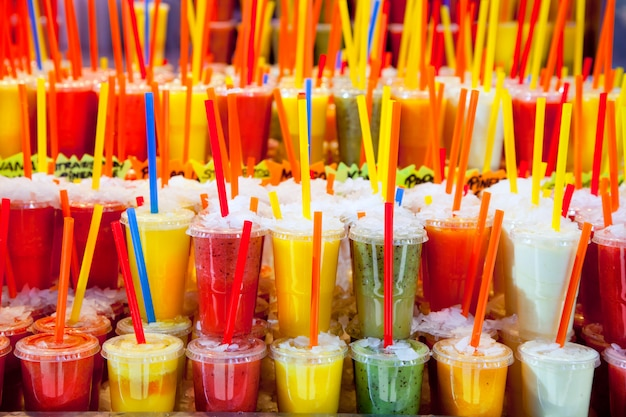 Colorful natural fresh fruits juice glasses with straw