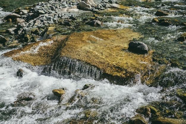 晴れた日の山川の乱流の大きな岩とカラフルな自然の背景。日差しの中で大きな石で水面のクローズアップ。速い川の美しい急流。マウンテンクリークのクローズアップ。