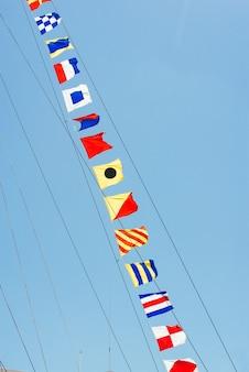 Красочные морские парусные флаги, развевающиеся на ветру от линий мачты парусника, подсвечиваются солнцем в ярко-синем небе.