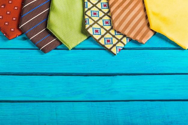 青い木製の背景にカラフルなネクタイ