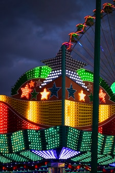 Colorful neon lights in star forms on the background of ferris wheel