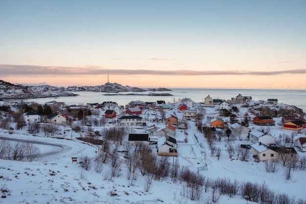 Lofoten 섬의 경계에서 겨울에 해안선에 덮여 눈이있는 다채로운 노르웨이 마을