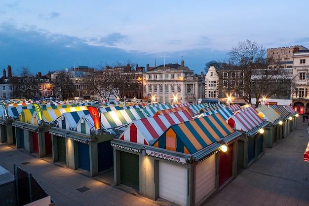 カラフルなノリッジマーケットとイギリス、イングランド、ノーフォークの夕暮れ時の有名な城