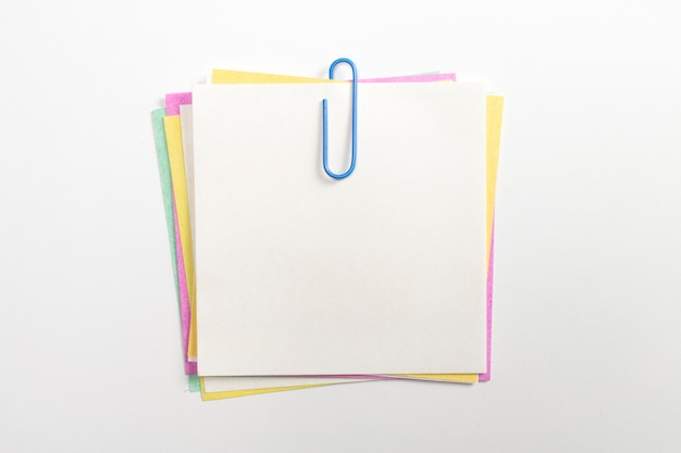 Colorful note paper pin with blue paper clips and isolated on white.