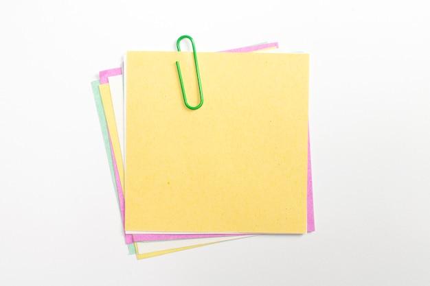 ペーパークリップと白で隔離されるカラフルなメモ紙ピン。