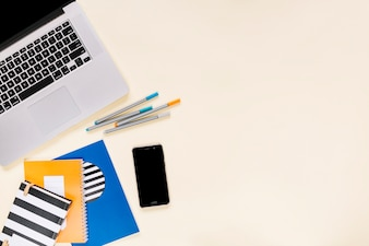 Colorful notebooks and felt-tip pens with cellphone and laptop on cream background