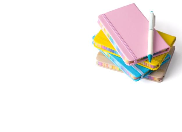 Красочные тетради при изолированная ручка. обратно в школу концепции.