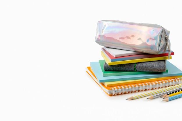 Красочные блокноты и карандаши на белом столе с копией пространства