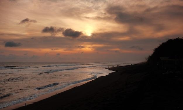 여름 동안 깊고 푸른 하늘과 태양 광선으로 다채로운 바다 해변 일몰