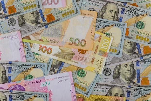 Разноцветные банкноты украинские счета национальной валюты и американские доллары деньги и финансы инвестиций.