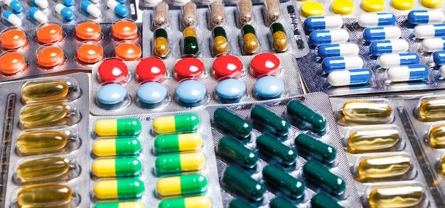 フレアライトで美しいパターンに配置されたブリスター包装のカラフルな錠剤やカプセルの丸薬。製薬業界の概念。薬局ドラッグストア。抗生物質耐性。