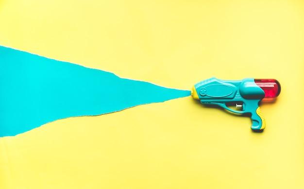 Красочный водяной пистолет на фоне цветной бумаги
