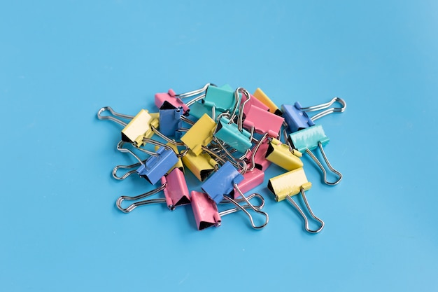 Colorful office paper clips on blue background.