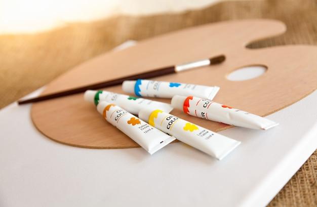 木製パレットの上に横たわるチューブと絵筆の中のカラフルな油絵の具