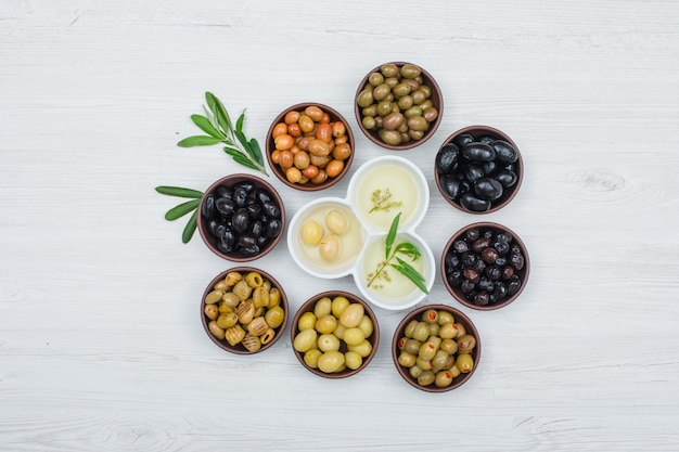 Colorful olives and olive oil with olive leaves in a clay and white bowls on white wood plank, top view.