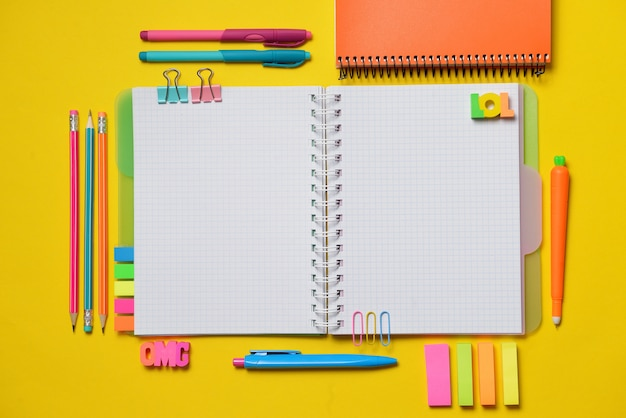 Colorful open copy book with office and student supplies on yellow chalk.