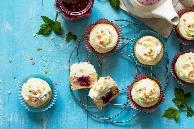 Colorful orange cupcake birthday with raspberry jam on a wooden table top view flat lay background