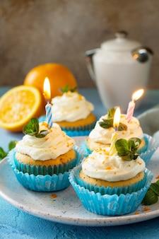 青い石またはスレートの背景に誕生日のキャンドルとカラフルなオレンジ色のカップケーキ