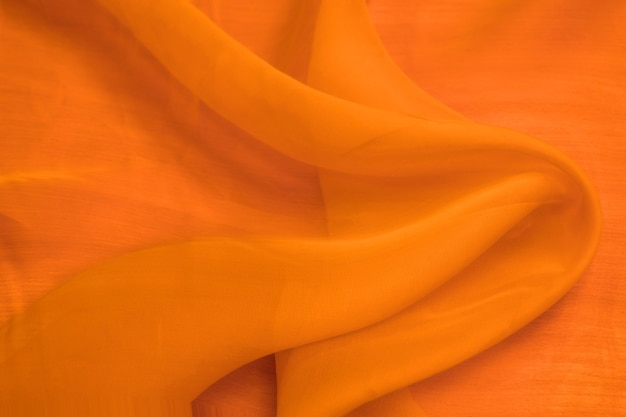 Colorful orange silk satin texture background, red cotton fabric cloth texture