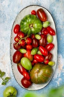 Красочные органические свежие помидоры в винтажной тарелке