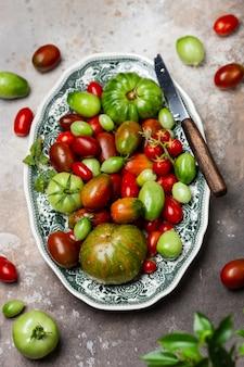 Красочные органические помидоры в винтажной тарелке