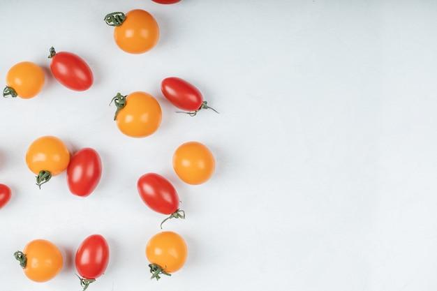 Красочные органические помидоры на белом фоне. фото высокого качества